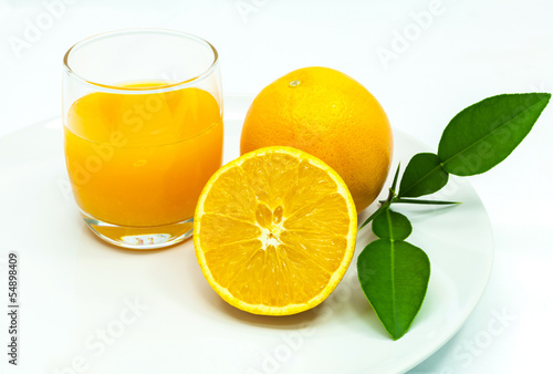 Glass of fresh orange juice with sliced orange .