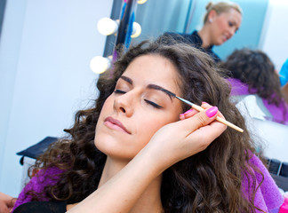woman putting mascara make up