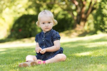 Kleines Mädchen sitzt auf Wiese