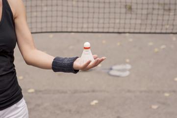 Girl holding a badminton shuttlecock