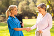 mid aged nurse handshaking senior patient