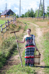 Girl with wooden rake and bucket on country road in village