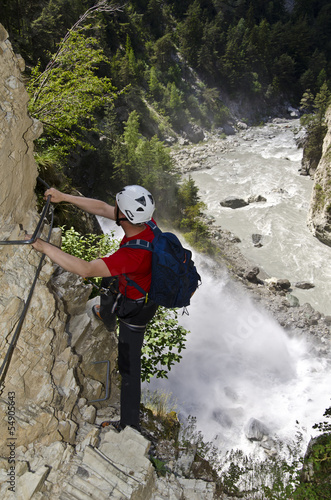 Hiker climbing a spectacular via ferrata near a waterfall