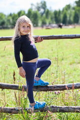 Small Caucasian girl standing on village fence at summer day