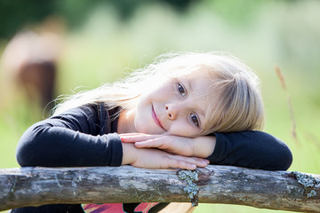 Blond hair girl with clasped hands resting in summer sunny day