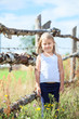 Caucasian small girl with closed eyes standing in front of fence