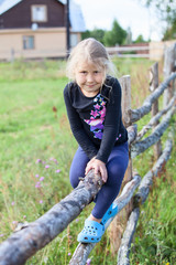 Countrygirl sitting on fence in village at summer day