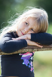 Tired blond hair small girl with clasped hands resting on fence