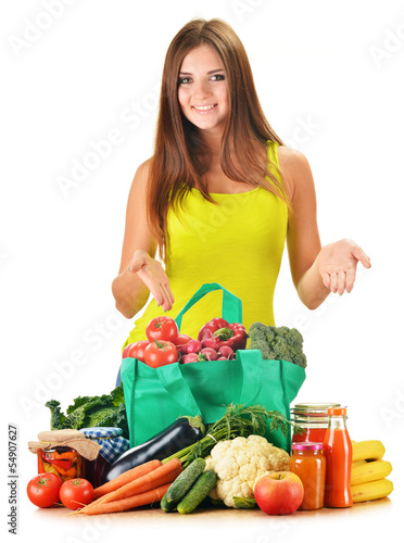 Young woman with variety of grocery products in shopping bag