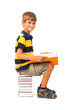 Schoolboy is sitting on books