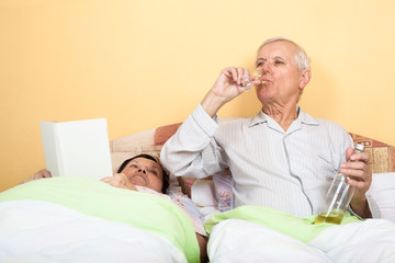 Senior man drinking alcohol in bed