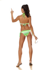 brunette in a bikini pointing a finger on imaginary object