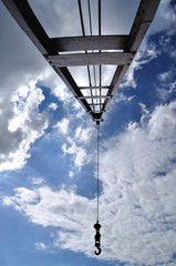 Crain with iron pendulum hook with blue sky.