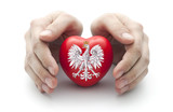 Hands covering Polish coat of arms on a red heart
