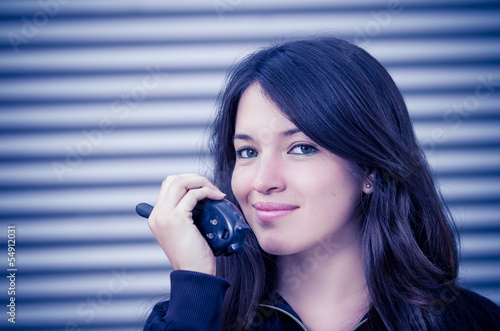 Businesswoman in warehouse using walkie-talkie
