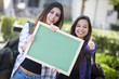 Mixed Race Female Students with Thumbs Up Holding Blank Chalkboa