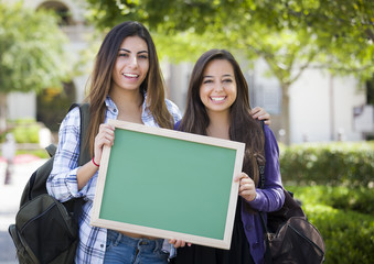 Mixed Race Female Students Holding Blank Chalkboard