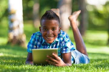 Outdoor portrait of student black boy using a tactile tablet - A