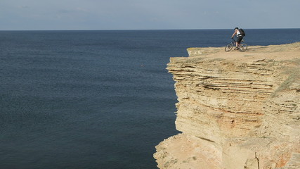 Traveler riding bicycle on cliff by sea