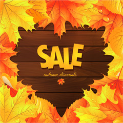 Sale. Autumn leaves on a wooden background