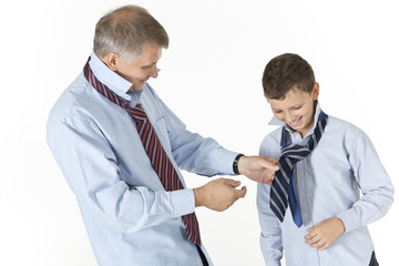 Father teaching his son to tie a knot on a tie