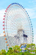 huge ferris wheel in Yokohama City under bright blue sky.