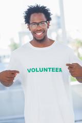 Cheerful man pointing to his volunteer tshirt