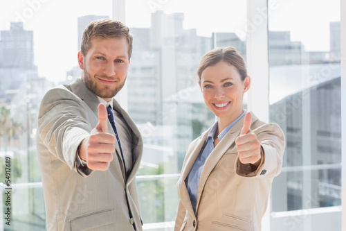 Smiling business team giving thumbs up