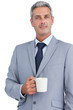 Confident businessman standing with coffee