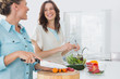 Cheerful women preparing salad together