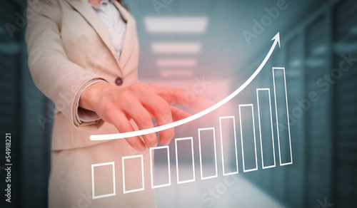 Businesswoman touching bar chart and arrow graphic