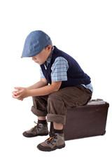 Junge sitzt traurig auf einem Koffer