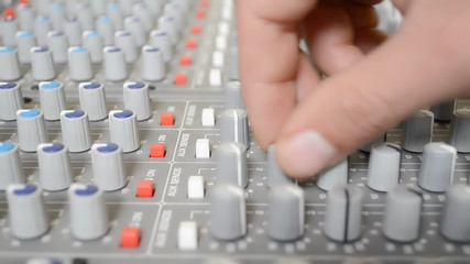 adjusting knobs on sound mixer