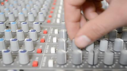 adjusting knobs on sound mixer