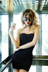 girl posing in elevator with cup of coffee