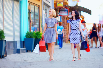 two elegant women walking colorful city street