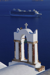 Santorini with church bell against boat in Greece