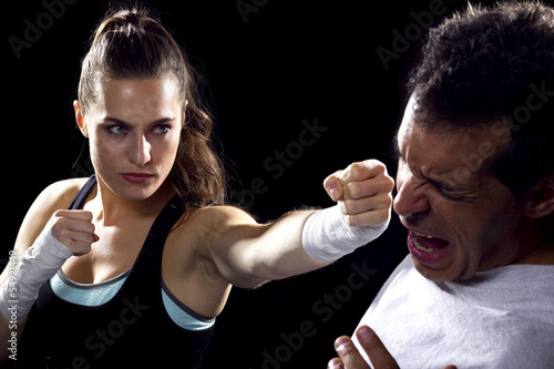 female MMA fighter fighting a man