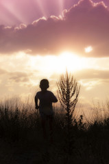 Silhouette of a child running at the sunset - 2