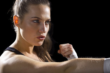 female MMA fighter punching.  black background