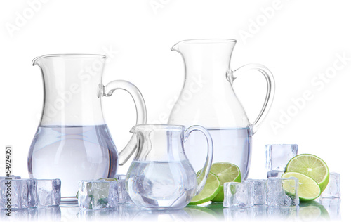 Glass pitchers of water with ice and lime isolated on white