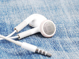 white earphone and jack on jeans background