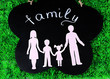 Family from paper on wooden board on bright background