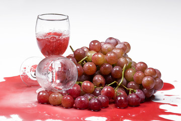 Red Wine in glass and red grapes on white background