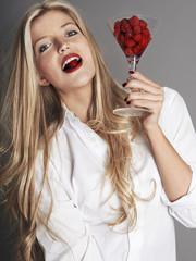 Pretty blonde girl holding glass of raspberries