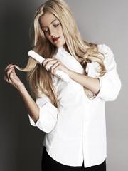 Pretty blonde girl with hair straightener