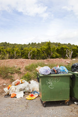Overflowing bins next to Orange Orchard, Valencia region, Spain