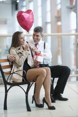 Man gives woman gift and heart shaped balloon