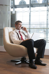 Businessman in arm chair working on laptop on the phone