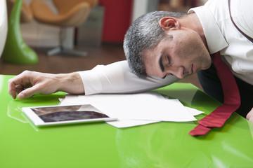 Businessman asleep on documents